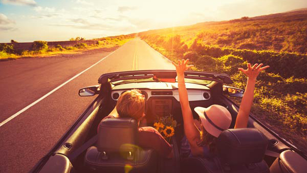Happy Young Couple Driving Along Country Road in Convertible at